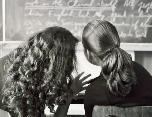 two girls in a classroom looking at the board